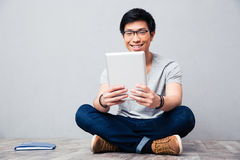 Smiling asian man using tablet computer Royalty Free Stock Photography
