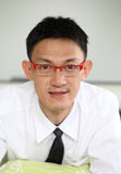 Smiling asian man wearing glasses sitting at the bedroom. Royalty Free Stock Photos