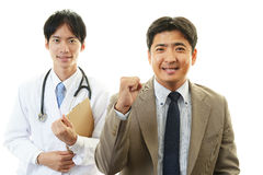Smiling Asian medical doctor and patient Royalty Free Stock Photo