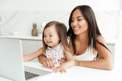 Smiling asian mother sitting with her little daughter and using laptop together Stock Images
