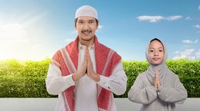 Smiling asian muslim father and daughter praying together stock photography