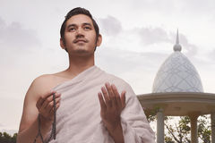 Smiling asian muslim man with ihram clothes holding prayer beads Royalty Free Stock Image