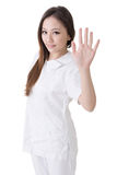 Smiling Asian nurse give a stop sign Royalty Free Stock Image