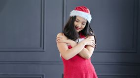 Smiling Asian Santa Claus woman posing at studio with gray background. Beautiful young festive girl standing with crossed hands looking at camera medium shot