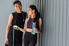 smiling asian sportswoman holding bottle of water and giving jump rope to young sportsman stock image