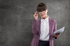 Smiling asian teacher with book standing stock photo