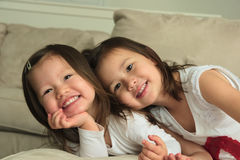 Smiling asian toddler sisters laying on stomach on couch Stock Images