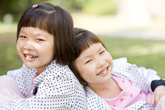 Smiling asian twin girls Royalty Free Stock Photos