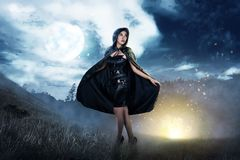 Smiling asian witch woman with black hooded cloak standing royalty free stock photography