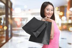 Smiling asian woman with bag shopping in black friday holiday. On the mall Stock Image