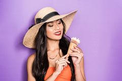 Smiling asian woman in beach attire holding an ice-cream cone in her hands. And looking aside royalty free stock photo