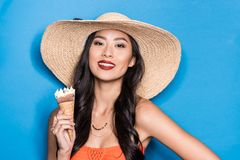 Smiling asian woman in beach attire holding an ice-cream cone and looking. At camera royalty free stock images