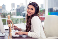 Smiling Asian woman on computer looking at the camera. In office Stock Image