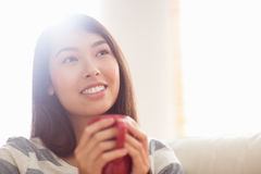 Smiling asian woman on couch having hot drink Royalty Free Stock Images