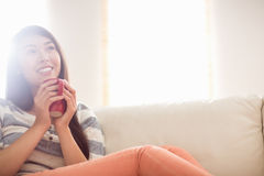 Smiling asian woman on couch having hot drink Royalty Free Stock Image
