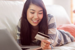 Smiling asian woman on couch using tablet to shop online Stock Photography