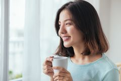 Free Smiling Asian Woman Drinking Coffee Relaxing On The Couch At Hom Royalty Free Stock Images - 105165869