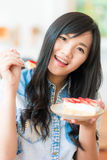 Smiling asian woman eating some strawberry cake in bakery cafe. Woman hold cake Stock Photography