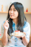 Smiling asian woman eating some strawberry cake in bakery cafe. Woman hold cake Royalty Free Stock Photography