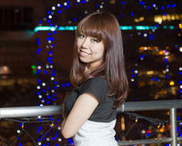 Smiling Asian woman in front of city lights Royalty Free Stock Photo