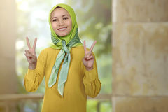 Smiling asian woman girl with hijab showing peace sign Royalty Free Stock Photos