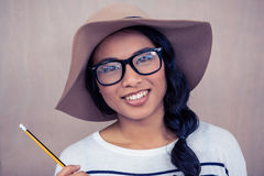 Smiling Asian woman with hat holding pencil Stock Photo
