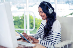 Smiling Asian woman with headphones using tablet Stock Images