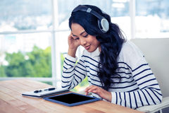 Smiling Asian woman with headphones using tablet Royalty Free Stock Images