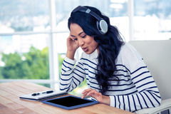 Smiling Asian woman with headphones using tablet Stock Photos