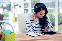 Smiling Asian woman with headphones using tablet Stock Image
