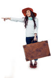 Smiling Asian woman holding luggage pointing somewhere Royalty Free Stock Image
