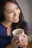 Smiling asian woman holding mug of coffee looking away Stock Images