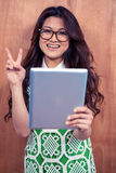 Smiling Asian woman holding tablet and making peace sign with hand Royalty Free Stock Images