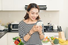 Smiling asian woman in the kitchen writing text message Stock Image