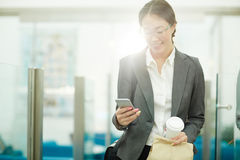 Smiling Asian Woman Leaving Office. Portrait of beautiful Asian businesswoman looking at smartphone screen and smiling while leaving office for coffee break royalty free stock photos