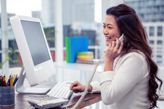 Smiling Asian woman on phone call using computer Royalty Free Stock Photography