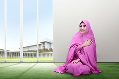 Smiling asian woman in pink veil sitting on carpet put her hand on chest and pray with all hearts inside the room royalty free stock photo