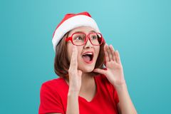 Smiling asian woman portrait with christmas santa hat shouting i Royalty Free Stock Photos