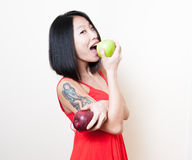 Smiling asian woman red dress biting green apple on white Royalty Free Stock Photos