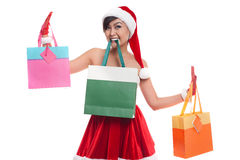 Smiling asian woman in red santa costume with shopping bags Royalty Free Stock Photo