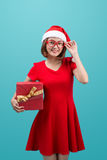 Smiling asian woman in red santa hat holding present box.  Royalty Free Stock Images