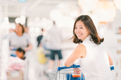 Smiling Asian woman with shopping cart or trolley at department store or shopping mall Royalty Free Stock Photos
