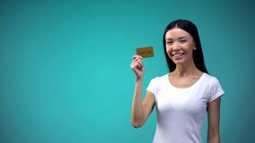 Smiling asian woman showing golden card into camera, limitless credit, banking. Stock photo stock photography