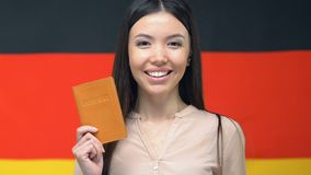 Smiling asian woman showing passport, standing against German flag, citizenship. Stock footage stock footage