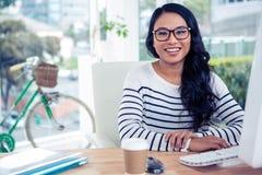 Smiling Asian woman sitting at desk posing for camera Royalty Free Stock Image