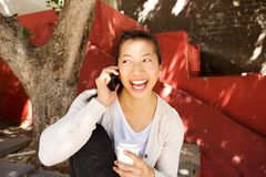 Smiling asian woman sitting outside and talking on cell phone Stock Images