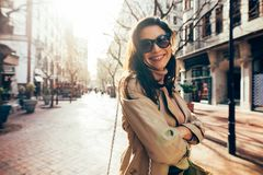 Stylish female model with sunglasses on city street. Smiling asian woman standing along the road in the city with her arms crossed. Stylish female model with Stock Photo