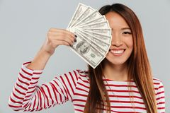 Smiling asian woman in sweater is covering in money Royalty Free Stock Images