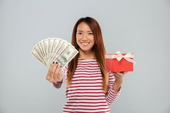 Smiling asian woman in sweater holding money and gift Royalty Free Stock Photo