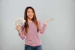 Smiling asian woman in sweater showing money and holding copyspace. On the pound over gray background Stock Image